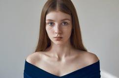 Skönhettema: stående av en härlig ung flicka med fräknar på henne framsida och bära en blå klänning på en vit bakgrund i studi arkivbilder