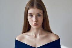 Skönhettema: stående av en härlig ung flicka med fräknar på henne framsida och bära en blå klänning på en vit bakgrund i studi royaltyfri bild