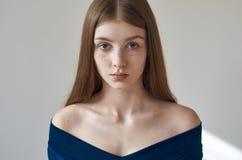 Skönhettema: stående av en härlig ung flicka med fräknar på henne framsida och bära en blå klänning på en vit bakgrund i studi royaltyfria bilder