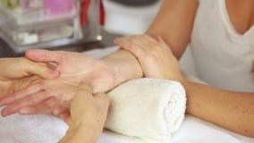 Skönhetterapeut som masserar kundhanden stock video