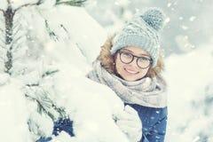 Skönhetvinterflickan som blåser insnöad frostig vinter, parkerar eller utomhus- arkivbilder