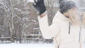 Skönhetvinterflickan som blåser insnöad frostig vinter, parkerar utomhus Flygsnöflingor lager videofilmer