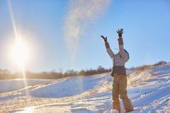 Skönhetvinterflickan som blåser insnöad frostig vinter, parkerar utomhus Flygsnöflingor solig dag Backlit Skönhetbarn arkivfoto