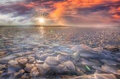 Skönhetvintersolnedgång över sjön med is Långsam exponering arkivbild