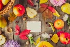Skörd- eller tacksägelsebakgrund med höstliga frukter, blommor, kalebassen och hälsningkortet på en lantlig trätabell Hösttappnin Arkivfoton