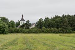 Skördad fält, skog och kyrka Royaltyfri Fotografi