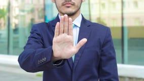 Skördaffärsman som gör en gest stoppet