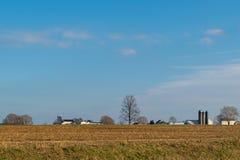 Skördat fält av havre, med träd och ett Amish lantgårdhus, på en härlig dag med blå himmel, Lancaster County, PA arkivbilder