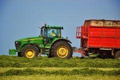 Skördearbetare som lastar av in i en traktorsläp Skördetröskan mejar fältet Lantbruktraktor som samlar höstacken slovakia Arkivfoto