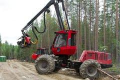 Skördearbetaremaskin som arbetar i en skog som lämnar för skogspåret arkivfoton