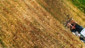 Skördetröska - flyg- sikt, surrsikt, modern skördetröska på det guld- vetefältet i sommaren royaltyfria foton