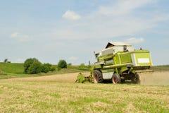 Skördetröska i vetefältet under plockning Royaltyfria Foton