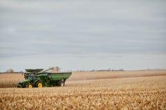 Skördetröska som fyller en traktorsläp royaltyfri foto