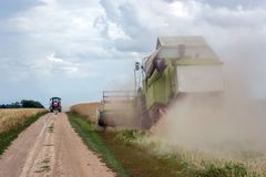 Skördetröskan våldtar, och traktoren går att lasta av det royaltyfri foto