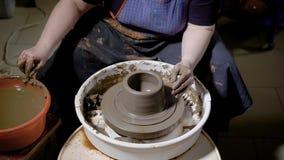 Skördhänder av den begåvade hantverkaren som formar lergods och gör krukmakeri på keramiker` s, rullar in seminariet arkivfilmer