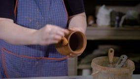 Skördhänder av det bärande förklädet för begåvad keramiker och att rymma härliga lergods i händer och anseende i hantverkstudio arkivfilmer