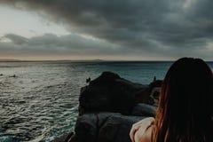 Skördkvinnaanseende på klippan nära havet royaltyfri bild