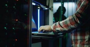 Skördman som arbetar på bärbara datorn i serverrum arkivfilmer