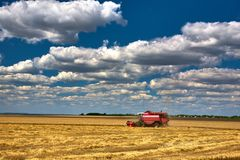 Skördtekniker harvester Jordbruksmark och att slutta fält på en ljus och solig dag i sommar royaltyfri foto