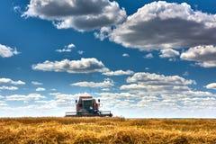 Skördtekniker harvester Jordbruksmark och att slutta fält på en ljus och solig dag i sommar arkivbilder