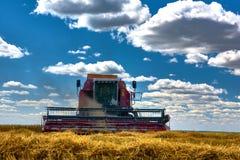 Skördtekniker harvester Jordbruksmark och att slutta fält på en ljus och solig dag i sommar arkivfoto