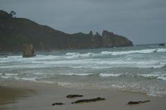 Sköt av vågorna som kommer till stranden och bort en härliga Cliff On The Beach Of El Aguilar på en regnig dag Juli 29, 2015 arkivfoton