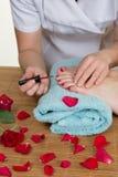 Sköt en bild av händer som kvinnlign som sätter en fernissa spikar på Royaltyfria Foton