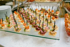 Sköta om - den tjänade som tabellen med olika mellanmål, canape och appetize royaltyfria foton