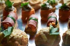 Sköta om den tjänste- bufféplattan med canapes och aptitretande smörgåsar Royaltyfria Bilder