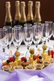 Sköta om portionbuffé med canape och champagne Arkivfoto