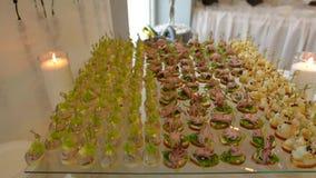 Sköta om smörgåsar på buffétabellen kött fisk, grönsakcanapes på en festlig gifta sig tabell, brinnande stearinljus lager videofilmer