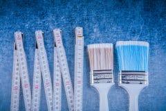 Skład drewniani metrowi farb muśnięcia na porysowany kruszcowym Obrazy Stock