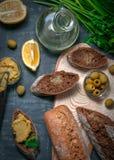 Skład dwa baguettes otręby i cała zbożowa mąka Kanapka hummus i oliwki Naczynie z jarzynowym olejem Na a fotografia stock
