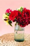 Skład kolorowe róże w wazie na łozinowej pielusze na różowym tle obraz stock