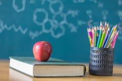 Skład materiały, książki i czerwony jabłko na biurku, Th zdjęcia royalty free