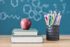 Skład materiały, książki i czerwony jabłko na biurku, Th obrazy royalty free