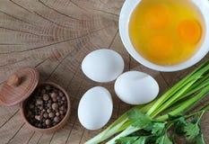Skład od foods jajko, yolk, pieprz, greenery, na drewnianym tle Rodzaj od above obraz stock