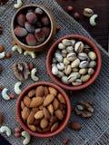 Skład od różnych rozmaitość dokrętki na drewnianym tle - migdały, nerkodrzewy, arachidy, orzechy włoscy, hazelnuts, pistacje Fotografia Royalty Free