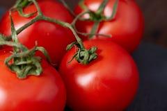 Skład pomidorowa wiązka i gorący pieprz na czarnym kawałku deska, odgórny widok, zakończenie Obraz Stock