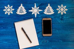 Skład telefon, smartphone, notatnik lub pióro dla pisać na błękitnym drewnianym tle z Bożenarodzeniowymi dekoracjami, Mieszkanie  zdjęcie stock