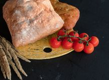 Skład warzywa i chleb w wieśniaku projektujemy na czarnym drewnianym stole Chlebowi pomidory ogórkowi obrazy stock