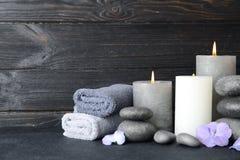 Skład z kamieniami, ręcznikami i świeczkami na stole przeciw drewnianemu tłu zen, fotografia stock