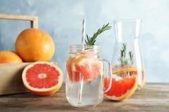 Skład z kamieniarza słojem natchnący grapefruits i woda obraz stock