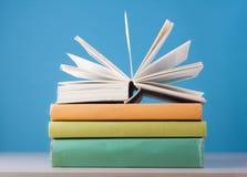 Skład z otwartą książką, hardback rezerwuje na drewnianym stołu i błękita tle tylna szkoły Edukaci tło Fotografia Royalty Free