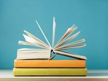 Skład z otwartą książką, hardback rezerwuje na drewnianym stołu i błękita tle tylna szkoły Edukaci tło Zdjęcia Royalty Free