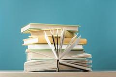 Skład z otwartą książką, hardback rezerwuje na drewnianym stołu i błękita tle tylna szkoły Odbitkowa przestrzeń dla teksta Obrazy Stock