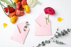 Skład z pięknymi ranunculus kwiatami, kopertami i obrazy royalty free