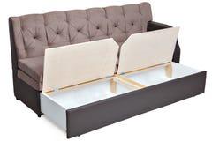 Składać jasnobrązowego tkaniny kanapy łóżko z magazynem fotografia stock