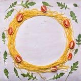 Składnika makaronu czereśniowych pomidorów surowy arugula wykładał ramę na drewnianej nieociosanej tło odgórnego widoku przestrze Zdjęcie Royalty Free