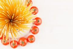 Składnika Włoskiego makaronu odgórny widok - snop spaghetti, czereśniowi pomidory, basil, ser na białej drewno desce z pustą kopi Obrazy Royalty Free